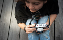 Hipster woman taking photos with retro film camera  on wooden floorof city park,beautiful girl photographed in the old camera Royalty Free Stock Photography