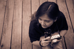 Hipster woman taking photos with retro film camera  on wooden floorof city park,beautiful girl photographed in the old camera Stock Photos