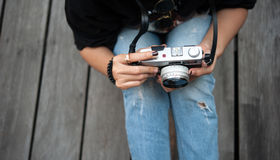 Hipster woman taking photos with retro film camera  on wooden floorof city park,beautiful girl photographed in the old camera Stock Image