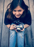 Hipster woman taking photos with retro film camera  on wooden floorof city park,beautiful girl photographed in the old camera Stock Photo