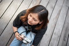 Hipster woman taking photos with retro film camera  on wooden floorof city park,beautiful girl photographed in the old camera Royalty Free Stock Photo