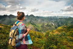 Hipster woman traveler with backpack enjoying beautiful view of Stock Image