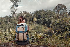 Hipster woman traveler with backpack looking at wild jungle Stock Photography