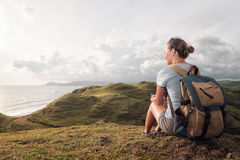 Hipster woman traveler with backpack  relax and enjoying sunset Stock Photos