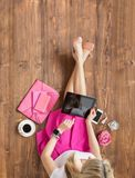 Hipster woman using tablet computer. While sitting on wooden  floor Royalty Free Stock Images