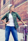 Hipster woman with vintage road bike on city street Stock Photos