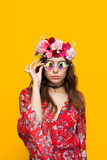 Hipster woman wearing flower chaplet touching glasses Stock Photos