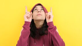 Hipster woman wearing a hood and pointing up stock video footage