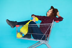 Hipster woman with yellow skateboard sitting in shopping trolley Royalty Free Stock Image