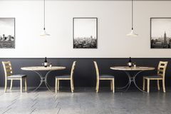 Hipster wooden cafe interior. Wooden cafe interior with concrete floor, round tables and gray and wooden chairs at monochrome wall with pictures. 3d rendering Royalty Free Stock Photography
