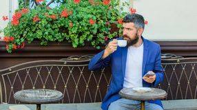 Hipster work business call. Business online sales. Manager always in touch. Man bearded businessman sit terrace with. Smartphone and cup of coffee. Take care of royalty free stock photo