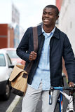 Hipster work commute. Young trendy black african hipster man with bicycle walking in urban city on way commute to work Stock Image