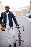 Hipster work commute. Young trendy black african hipster man with bicycle walking in urban city on way commute to work Royalty Free Stock Images
