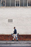 Hipster work commute. Young trendy black african hipster man with bicycle walking in urban city on way commute to work Royalty Free Stock Image