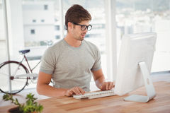 Hipster working on computer at desk Stock Photography