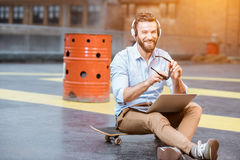 Hipster working with laptop on the rooftop. Handsome hipster businessman working with laptop sitting on the skateboard on the rooftop background. Lifestyle Royalty Free Stock Photography