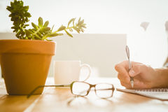 Hipster writing on book at desk in office Royalty Free Stock Photography