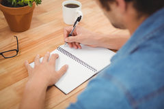 Hipster writing on spiral book at desk Royalty Free Stock Images