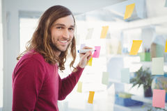 Hipster writing on sticky note stuck on glass Stock Photography
