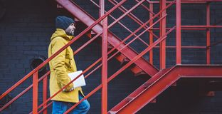 Hipster with yellow backpack, jacket and cap rises on red retro ladder with computer in hands, freelance holding laptop in spring. Street outdoor, tourist man royalty free stock photography