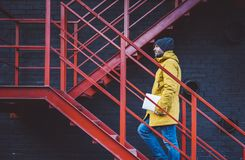Hipster with yellow backpack, jacket and cap rises on red retro ladder with computer in hands, freelance holding laptop in spring. Street outdoor, tourist man royalty free stock photo
