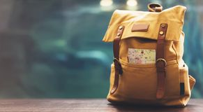 Hipster yellow backpack and map closeup. View from front tourist traveler bag on background blue sea aquarium. Person hiker. Visiting oceanarium museum on royalty free stock image