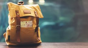 Hipster yellow backpack and map closeup. View from front tourist traveler bag on background blue sea aquarium. Person hiker visiti. Ng oceanarium museum in royalty free stock photography