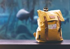Hipster yellow backpack and map closeup. View from front tourist traveler bag on background blue sea aquarium. Person hiker visiti. Ng oceanarium museum on royalty free stock photos