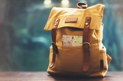 Hipster yellow backpack and map closeup. View from front tourist traveler bag on background blue sea aquarium. Person hiker visiti. Ng oceanarium museum on royalty free stock photography