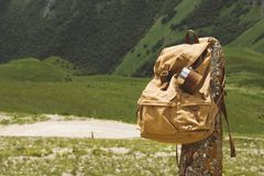 Hipster yellow vintage backpack with a mug fixed on it with a mug close-up front view. Traveler`s travel bag in the. Background of a mountain landscape royalty free stock photography