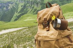 Hipster yellow vintage backpack with a mug fixed on it with a mug close-up front view. Traveler`s travel bag in the. Background of a mountain landscape stock images