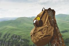 Hipster yellow vintage backpack with a mug fixed on it with a mug close-up front view. Traveler`s travel bag in the. Background of a mountain landscape stock photos