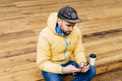 Hipster young bearded man wearing yellow jacket, stylish black cap and jeans sitting at wooden floor holding smartphone listening. To music with earphones stock photos