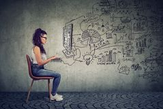 Hipster young business woman working in an office on computer. Brainstorming a start up plan stock images