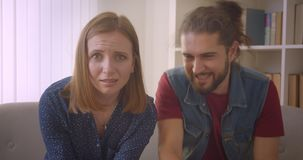 Hipster young couple playing videogame while the girl fails and gets sad and boyfriend kisses her to recompose. Hipster young couple playing videogame while the stock video footage