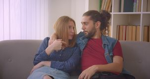 Hipster young couple watching comedy movie on TV and laughing cheerfully at home. Hipster young couple watching comedy movie on TV and laughing cheerfully at stock footage
