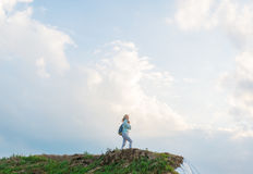 Hipster young girl with backpack enjoying sunset on peak of hill. royalty free stock image