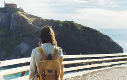 Hipster young girl with backpack enjoying sunset on seascape on peak mountain. Tourist traveler on background valley landscape vie Royalty Free Stock Photos