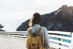 Hipster young girl with backpack enjoying sunset on seascape on peak mountain. Tourist traveler on background valley landscape vie Royalty Free Stock Images