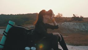 Hipster young girl with backpack on the top of a rock uses virtual reality glasses in the sunset. Active modern. Futuristic lifestyle leisure concept stock footage