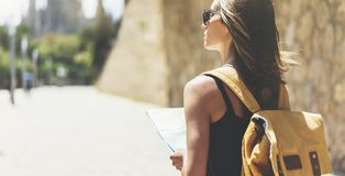 Hipster young girl with bright backpack and fashion sunglasses looking at map. Said view tourist traveler on background sun city. Person visiting the sights royalty free stock image