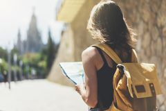 Hipster young girl with bright backpack and fashion sunglasses looking at map. Said view tourist traveler on background sun city. Person visiting the sights royalty free stock images