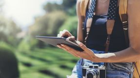 Hipster young girl with bright backpack and vintage camera using tablet or holding gadget, planning travel plan. View tourist. Traveler with sunglasses on stock image
