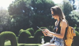 Hipster young girl with bright backpack and vintage camera using tablet or holding gadget, planning travel plan. View tourist. Traveler with sunglasses on royalty free stock images