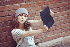 Hipster young girl makes a selfie using your tablet Royalty Free Stock Images