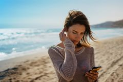 Hipster young girl photograph on smart phone gadget in sand coastline, blogger hold and using in female hand mobile screen stock photo