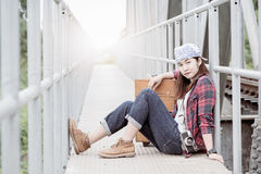 Hipster young girl sit on bridge railway with vintage luggage Royalty Free Stock Image