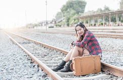 Hipster young girl smile and waiting train on railway background. Concept travel and leisure Stock Photography