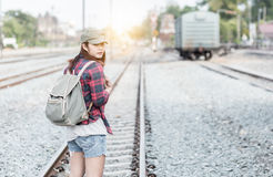 Hipster young girl waiting train on railway background. Stock Image