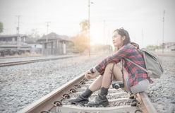 Hipster young girl waiting train on railway. Background and vintage tone, concept travel and leisure Stock Images